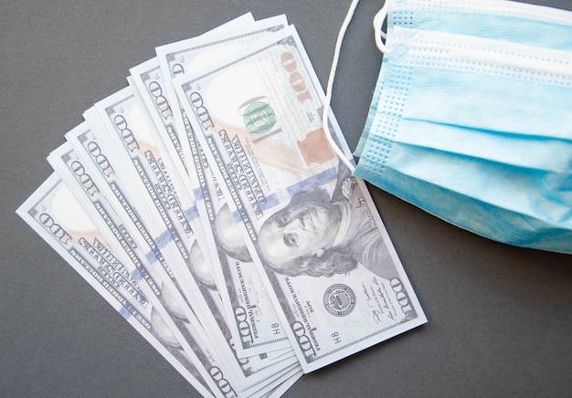 Голубая медицинская маска с долларами на темной поверхности. концепция covid-19.