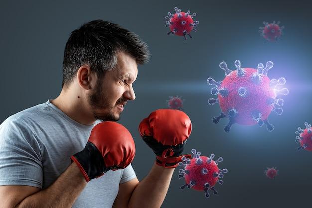 手袋をした男性ボクサーがcovid-19ウイルスの粒子と戦う。パンデミック、ワクチンの概念。