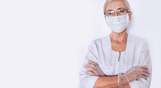 高齢者の成熟した女性医師や看護師は、白い医療コート、手袋、白い背景で隔離の個人用保護具を身に着けているフェイスマスクで腕を組んだ。ヘルスケアおよび医学の概念。 covid-1