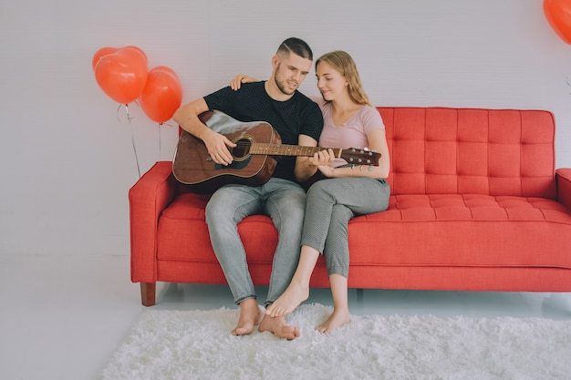 ギターを弾く男性女性カップルは家にいて安全なコロナウイルスcovid 2019