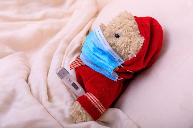 Мишка в медицинской маске в постели. респираторная медицина. дети и болезнь концепция болезни covid-2019.