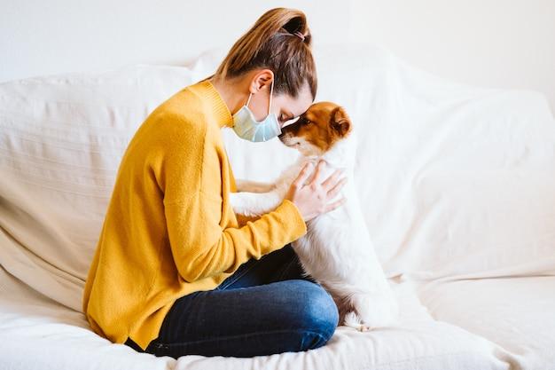 自宅でかわいい小さな犬を抱いて、ソファに座って、防護マスクを着た若い女性。コロナウイルスcovid-2019中の在宅コンセプト