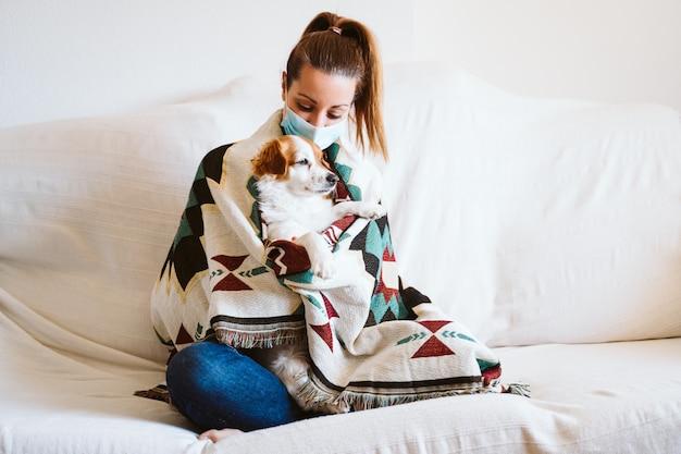 Молодая женщина, обнимая ее милая маленькая собака дома, сидя на диване, носить защитную маску. пребывание дома концепции во время коронавируса covid-2019