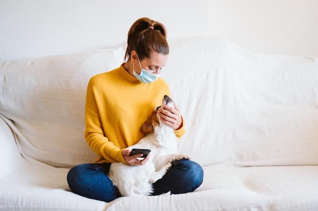 Молодая женщина с помощью мобильного телефона, милая маленькая собака, кроме того. сидеть на диване, надевать защитную маску. пребывание дома концепции во время коронавируса covid-2019