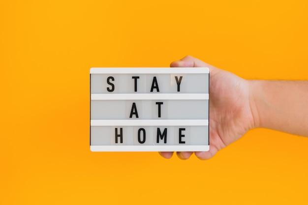 テキストを示す男性の手は、黄色の壁に分離された白いライトボックスに家に滞在します。コロナウイルスを止めます。自宅で検疫。 covid 2019