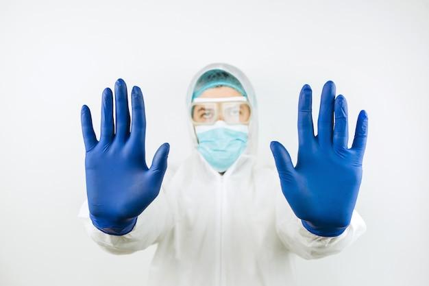 医療マスク、オーバーオール、青い手袋の医師。 covid 2019の流行を阻止します。医者は彼の手で一時停止の標識を示しています。