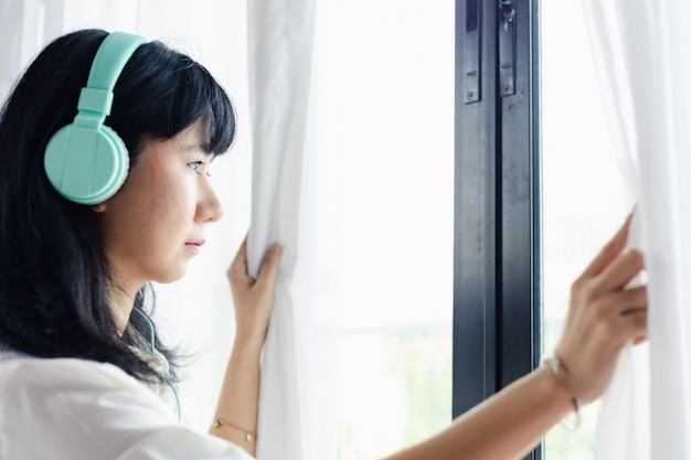 アジアの女性が家に滞在し、ヘッドフォンを身に着け、ドアにぼんやりと立って、自己検疫とコロナウイルスまたはcovid-2019の発生状況の概念における社会的距離を隔てる