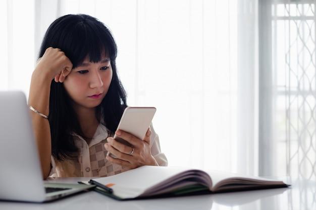 アジアの女性はコンピューターのラップトップでスマートフォンを使用して、ビジネス、自己検疫、家にいて、コロナウイルスやcovid-2019発生状況の概念で社会的距離を置くために家で働いています。