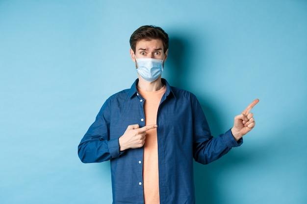 Covid и концепция здравоохранения. обеспокоенный молодой человек в медицинской маске поднимает бровь, указывая пальцем вправо с сомнительным и нервным лицом, стоя на синем фоне.