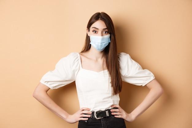 ベージュの背景に立っているカメラに警戒している医療マスクのcovidとライフスタイルのコンセプトの女性...