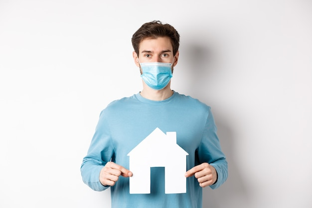 Covid 및 부동산 개념. 평면에 대 한 검색, 종이 집 컷 아웃을 보여주는, 의료 마스크를 쓰고, 흰색 배경에 서있는 남자.