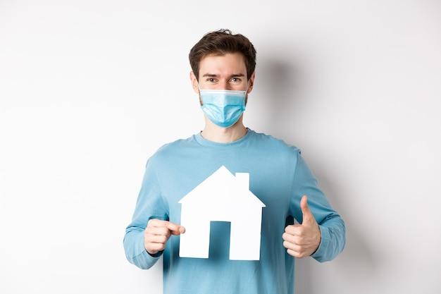 Covid 및 부동산 개념. 웃는 기관 클라이언트 엄지 표시 및 종이 집 컷 아웃, 의료 마스크를 쓰고 좋은 거래를 승인합니다.
