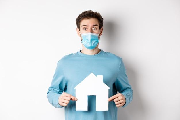 Covid 및 부동산 개념. 카메라, 흰색 배경보고 종이 집 컷 아웃을 보여주는 의료 마스크에 놀란 된 남자.
