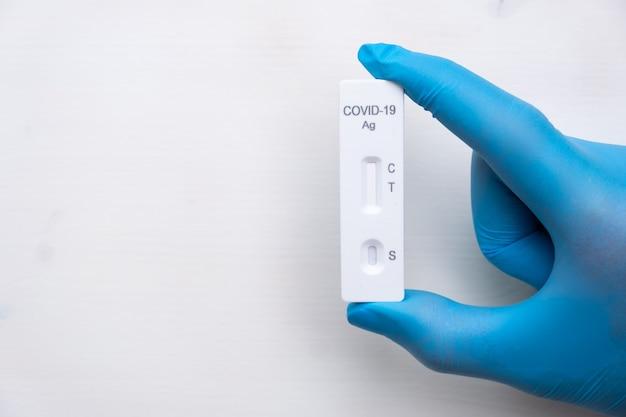 コピー付きのゴム手袋を手にした医師の病気を迅速に検出するためのcovid抗原検査