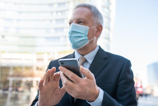 Covidコンセプト、都市の屋外で彼のスマートフォンを使用してマスクされた年配のビジネスマン