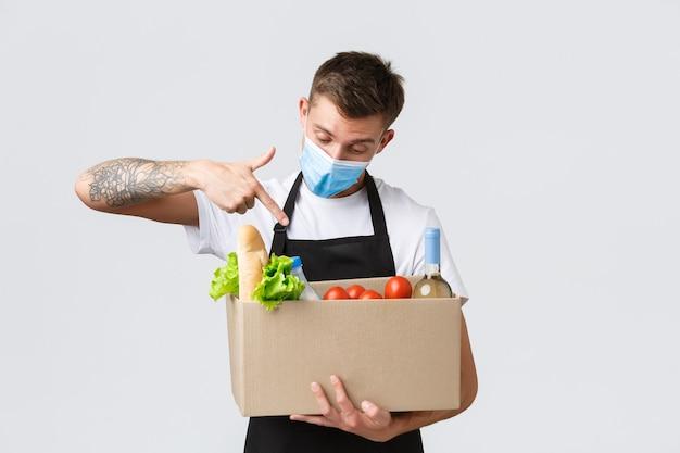 Concetto di spesa senza contatto covid e consegna di generi alimentari bel venditore in maschera medica che punta...