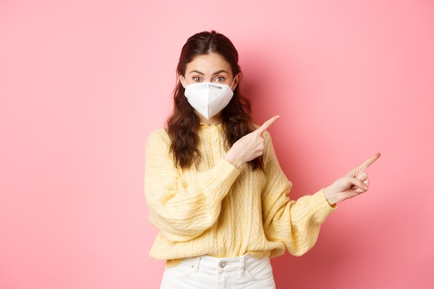 Covid corona and social distancing concept excited female model in respirator shows you advertisement points at logo aside wears medical respirator on face pink wall