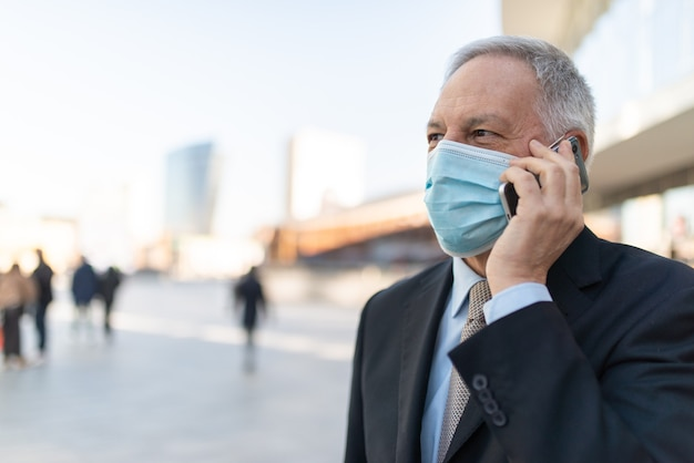 Covidコロナウイルスの概念、屋外で彼のスマートフォンで話しているマスクされた年配のビジネスマン