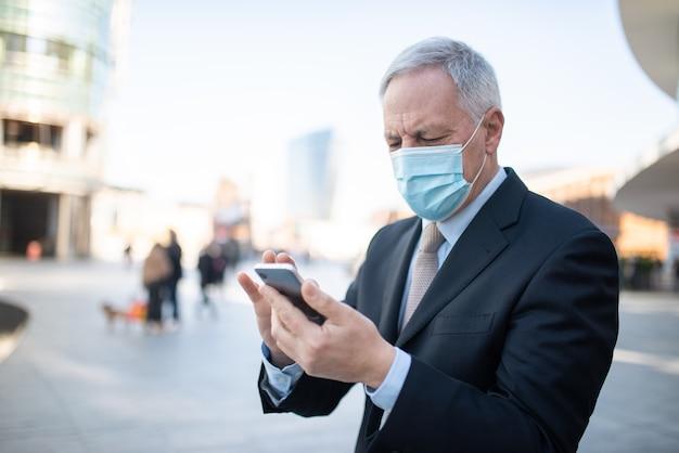 Covidコロナウイルスの概念、屋外で彼のスマートフォンを使用してマスクされた年配のビジネスマン