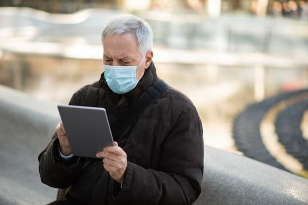 Covidコロナウイルスのライフスタイル、街の広場で屋外に座っている間彼のタブレットを使用してマスクされた年配のビジネスマン