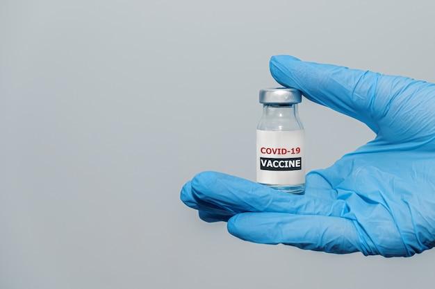 Вакцина против коронавируса covid в руке врача с защитными перчатками