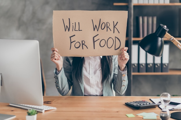 Covid economics poverty crisis concept. despair frustrated girl need job hold cardboard text will work for food wear jacket blazer sit table desk in workplace workstation