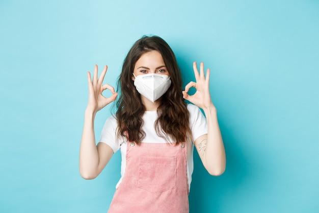 코비드, 건강 및 전염병 개념. 인공호흡기에 만족한 아름다운 소녀, 승인에 괜찮은 표시를 보여주는 의료 마스크, 코로나바이러스 예방 조치, 파란색 배경.