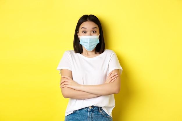 Covid, здравоохранение и концепция пандемии. азиатская женщина в белой футболке и медицинской маске скрещивает руки на груди и удивленно смотрит в камеру.