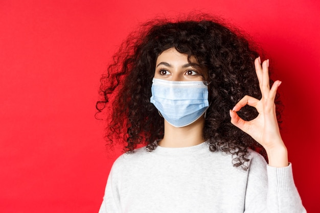 Covid and health concept image of young woman in medical mask approve promo showing okay gesture and...