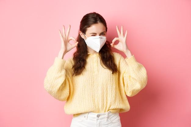 Изоляция коронавируса и концепция пандемии молодая улыбающаяся девушка уверяет, что вы подмигиваете и показываете знак «хорошо», или одобряете жест в медицинском респираторе, стоящий над розовой стеной