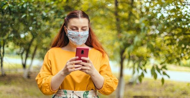 携帯電話を使用して歩く街の幸せな女性に必須のcovidマスク着用