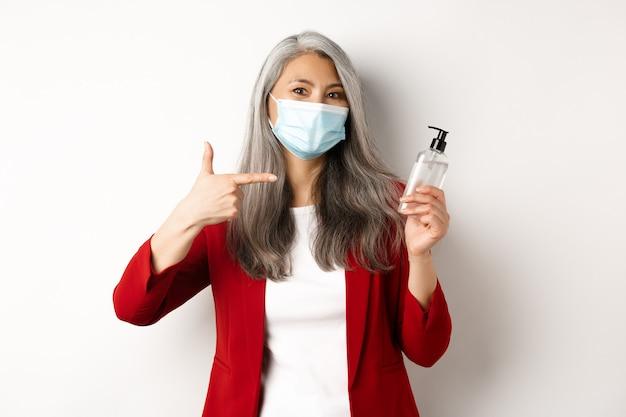 Covid, пандемия и бизнес-концепция. азиатская женщина-менеджер в маске для лица, указывая пальцем на дезинфицирующее средство для рук, рекомендуя антисептик, белый фон.