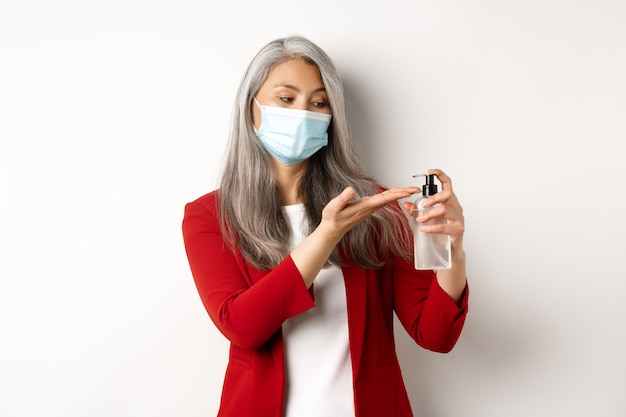Covid, пандемия и бизнес-концепция. деловая женщина в красном пиджаке и маске с использованием дезинфицирующего средства для рук для очистки и дезинфекции, стоя на белом фоне.