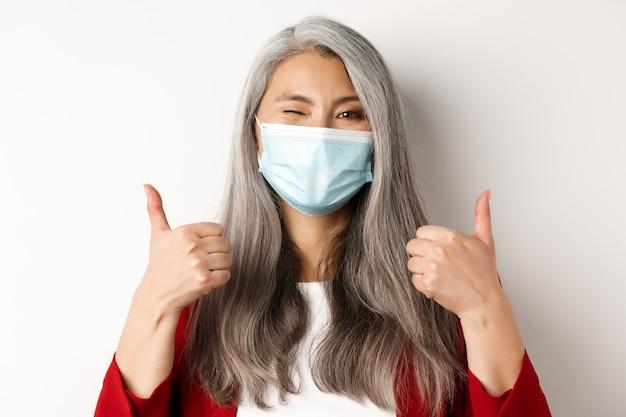 Covid、パンデミック、ビジネスコンセプト。医療マスク、ウィンクと承認で親指を立てて、白い背景で陽気なアジアの実業家。