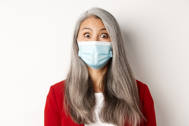 Covid, пандемия и бизнес-концепция. закройте удивленной азиатской бабушки в медицинской маске, поднимающей брови, глядя на камеру, на белом фоне.
