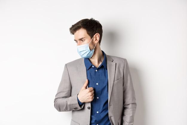 Covid、パンデミック、ビジネスコンセプト。スタイリッシュなスーツと医療マスクを身に着けているハンサムな男性起業家、脇を見て、白い背景。