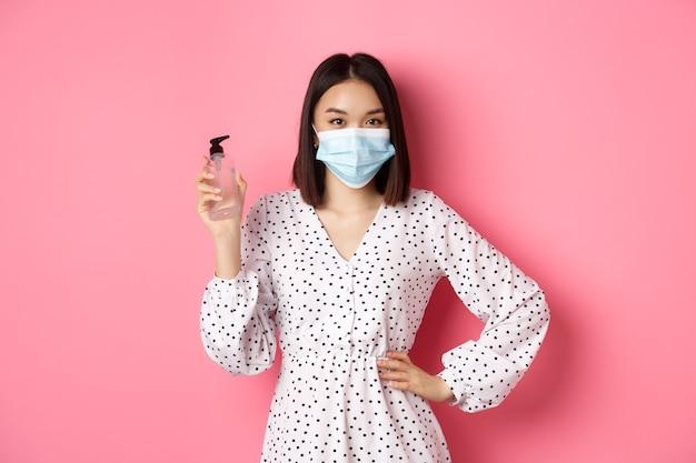 Пандемия covid и концепция образа жизни красивая кореянка в платье и медицинской маске показывает руку ...
