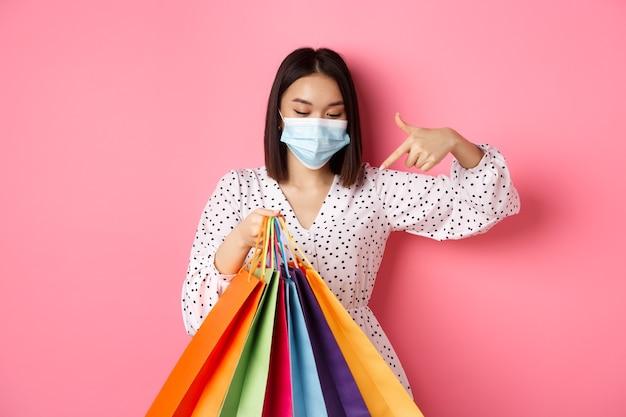 買い物袋を指している医療マスクのcovidパンデミックとライフスタイルのコンセプトかわいい韓国人女性...