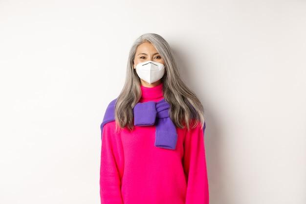 Covid、パンデミック、社会的距離の概念。カメラに微笑んでいるフェイスマスク、コロナウイルスからの予防策、白い背景の陽気なアジアのシニア女性モデル。