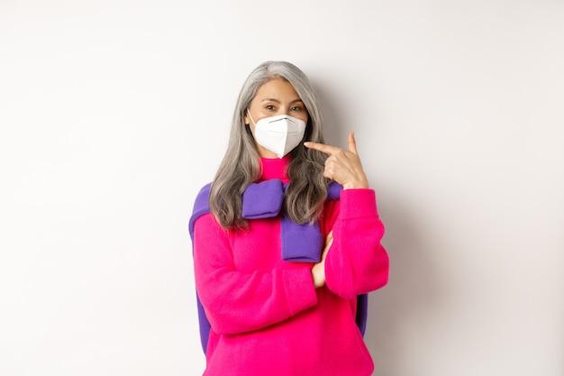 코비드, 전염병 및 사회적 거리 개념. 인공 호흡기를 착용하고 얼굴 마스크를 가리키고 웃고, 흰색 배경 위에 서 있는 세련된 아시아 수석 여성.