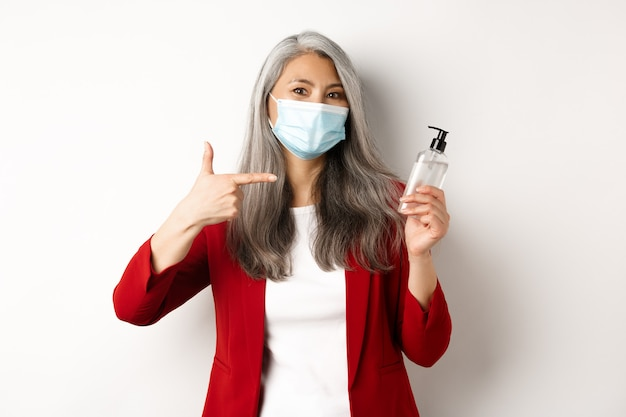 Covid, pandemic and business concept. asian female manager in face mask, pointing finger at hand sanitizer, recommending antiseptic, white background.