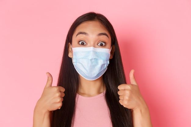 Covidパンデミックコロナウイルスと興奮して驚いたかなりアジア人の社会的距離の概念のクローズアップ...