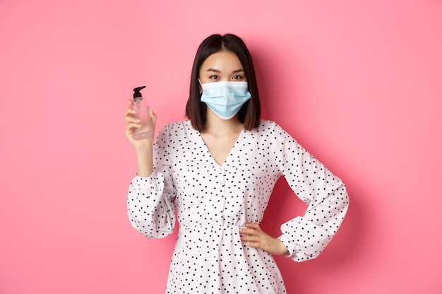 Pandemia di covid e concetto di stile di vita bella donna coreana in abito e maschera medica che mostra la mano s...