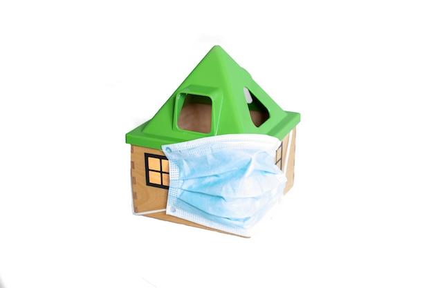 Covidパンデミック検疫コロナウイルス分離された白い背景の医療マスクのおもちゃの家