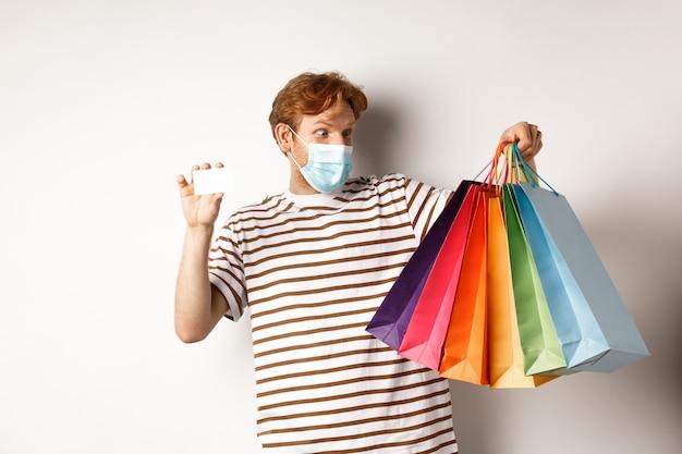 Covid, карантин и концепция образа жизни. пораженный рыжий мужчина, глядя на сумки после покупки с пластиковой кредитной картой банка, на белом фоне.