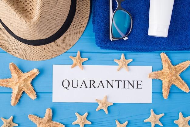 Covid検疫と海岸での休暇のコンセプト。青い木製の背景で隔離の検疫ワードヒトデタオルサングラス帽子と日焼け止めの俯瞰図のクローズアップ写真の上の上