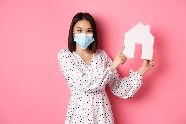 Covid концепция недвижимости и образа жизни милая азиатская женщина в маске продает дома, показывая модель о ...