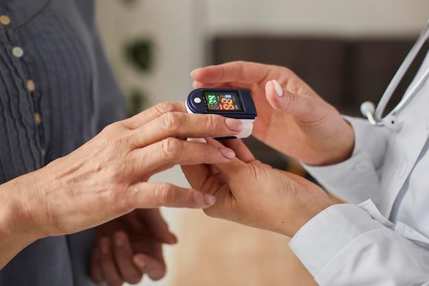 Женщина-врач центра восстановления covid проверяет уровень кислорода у пожилого пациента