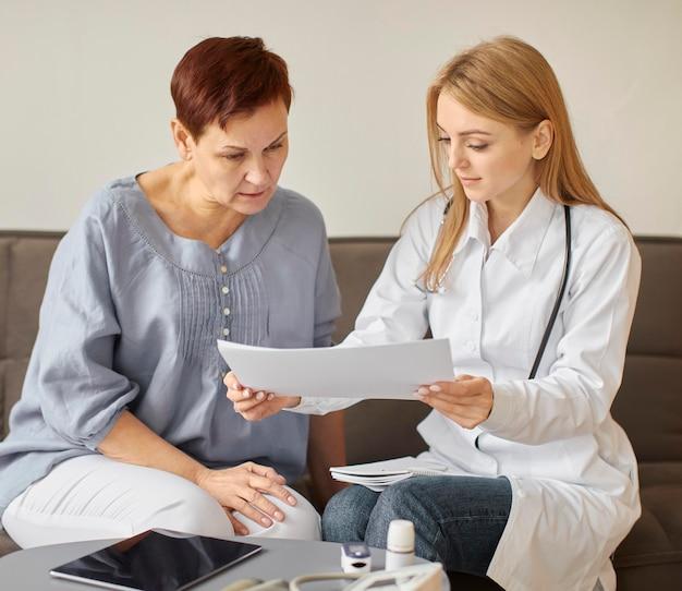 Женщина-врач центра восстановления covid проверяет результаты здоровья с пожилым пациентом