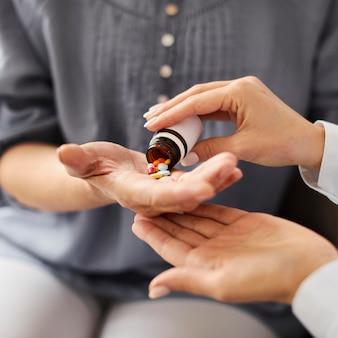 Medico femminile del centro di recupero di covid che dà le pillole del paziente anziano in mano